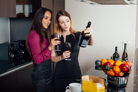 Two female friends catching up while drinking wine at home