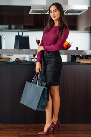 Full-length portrait of young stylish woman with shopping bags standing in the kitchen