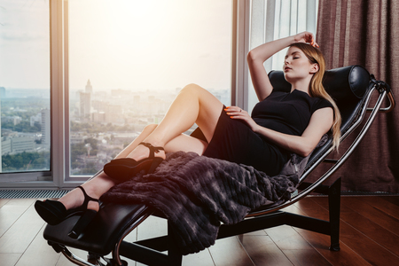 Portrait of female model wearing short black dress and high heels relaxing on chair Imagens