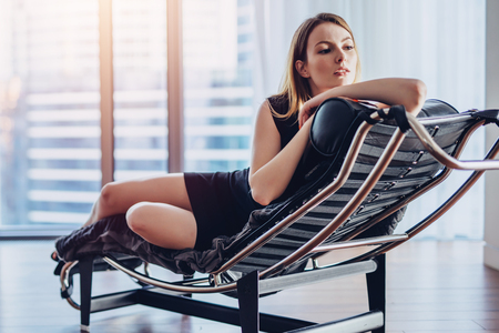 Elegant young woman with fair hair in little black dress lying on armchair supporting her head with hand looking out the panoramic window enjoying cityscape Imagens