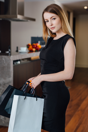 Smiling young woman posing with shopping bag happy with her purchase at home