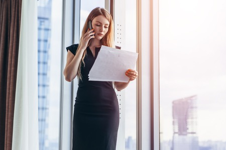 Elegant young female business owner holding documents talking on mobile phone discussing contract conditions standing in office.