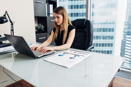 Woman working with documents sitting at desk in office