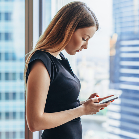 Confident young female using apps on mobile phone standing near big window in modern office Imagens