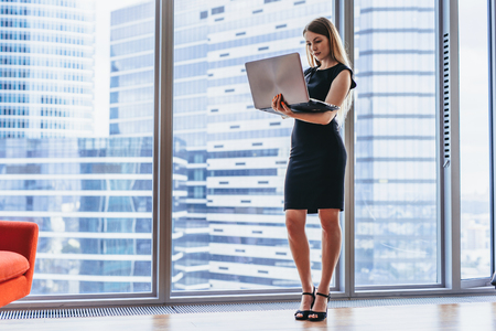 Businesswoman holding laptop standing in modern office against window with city view Imagens