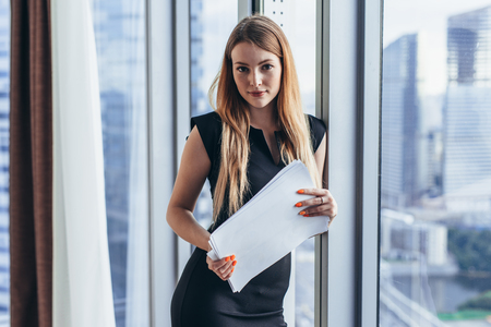 Portrait of pretty young woman holding documents looking at camera standing in office Imagens