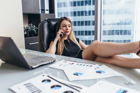 Confident female chief executive talking on phone while sitting with her feet on desk at work Imagens