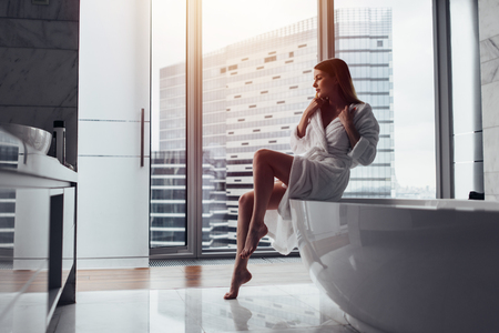 Back view of young woman wearing white bathrobe standing in bathroom looking out the window with bathtub in foreground Stockfoto