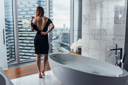 Back view of young woman wearing white bathrobe standing in bathroom looking out the window with bathtub in foreground Imagens