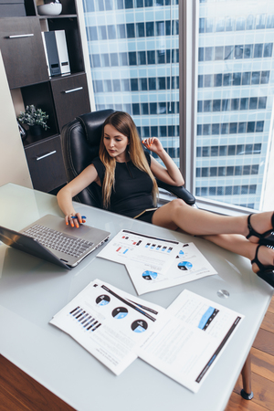 Portrait of relaxed female boss sitting at workplace with feet on table planning her workday writing goals in notebook Imagens