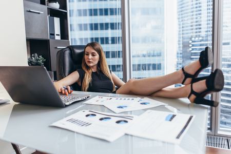 Woman sitting at desk with legs on table working on laptop analyzing financial statistics of the company Imagens