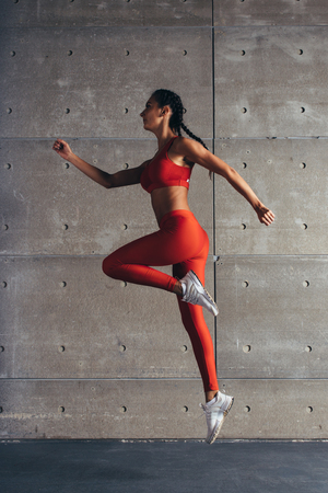 Young fit woman jumping while running Fitness sport girl exercising. Imagens