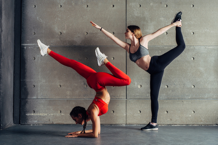 Two young fit women posing in studio.