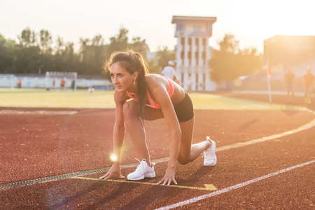 Woman in starting position ready for running in stadium.