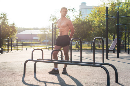 Fitnes man posing on street fitness station showing his muscular body Full lenght portrait. Zdjęcie Seryjne