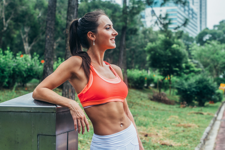 Slim fitness brunette woman with six pack abs wearing pink sport bra standing in city park relaxing after workout looking away from the camera Stock Photo