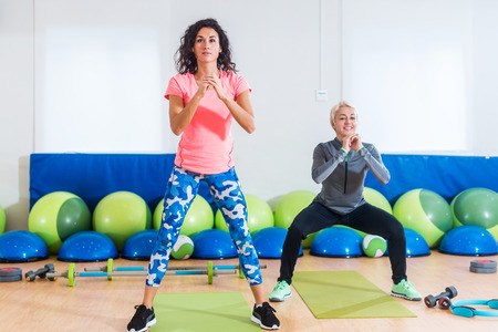 Two women in sportswear doing bodyweight squats while training indoors at sports hall