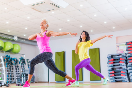 Two smiling female fitness models working out in gym or studio, doing cardio exercise.