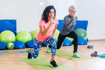 Two slim Caucasian women exercising on mats doing lunges with arms out in front of them in fitness club Stock Photo