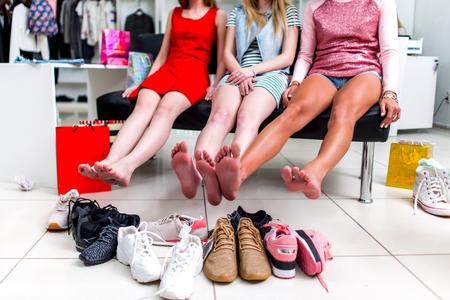 Jonge lachende vriendinnen zitten in een kledingwinkel kijken naar hun voeten en stapel nieuwe schoenen en lachen Stockfoto