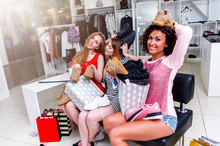Best friends doing shopping together fooling around with new shoes laughing putting them on head sitting in fashion store Stock Photo