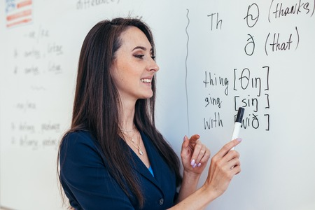 Teacher near whiteboard explains the rules. Learn foreign language. Stock fotó