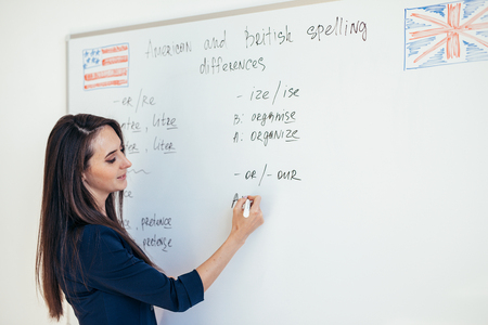 Teacher explaining differences between American and British spelling writing on whiteboard English language school