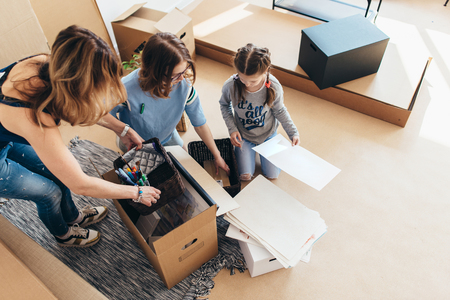 Family packing boxes in new home on moving day