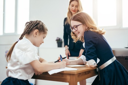 Portrait of schoolgirls talking during lesson in classroom