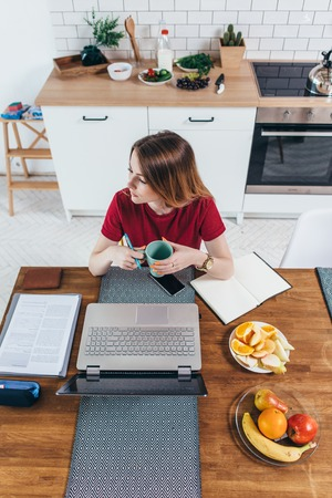 Woman holding cup sitting at table with laptop front of her in the kitchen. Imagens
