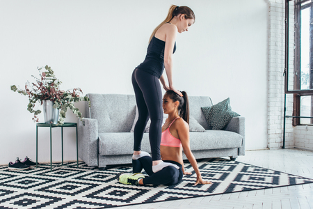 Woman helping friend in leg stretching workout at home Stok Fotoğraf