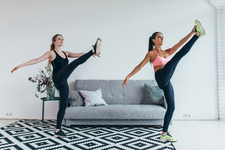 Fit woman stretching legs warming up workout at home