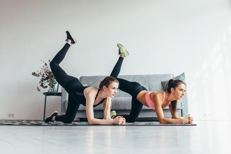 Two fit women doing bent knee donkey kick exercise in all fours position working out their buttocks at home