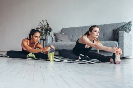 Fit women doing stretching while sitting on the floor at home Stock Photo