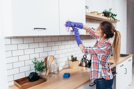 Woman in gloves cleaning cabinet with rag at home kitchen. Фото со стока
