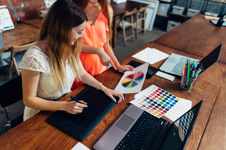 Female designer working with client at desk in her office