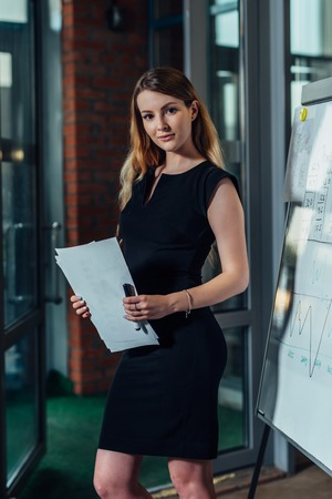 Portrait of young female entrepreneur wearing formal dress holding the financial report standing in the office