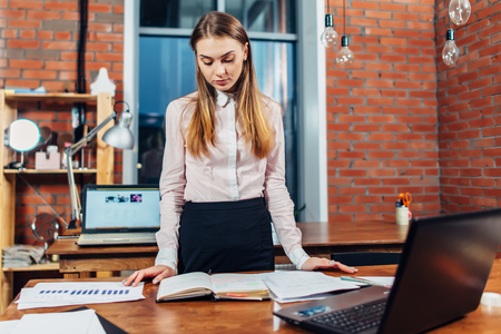 Female manager standing at her workplace planning her working day reading notes made in notebook
