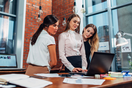 Woman with laptop colleagues standing in office