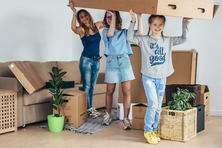 Woman and her daughters moving in new home Imagens