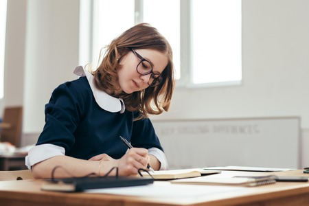 School Girl writes in a notebook sitting at table Classwork, homework Stock Photo