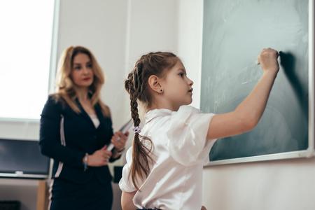 Schoolgirl first-grader writing on chalkboard. School lesson Teacher and pupil. Imagens