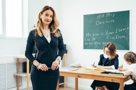 Teacher looking at camera standing in classroom