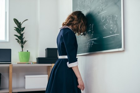 Sad schoolgirl standing in front of blackboard.