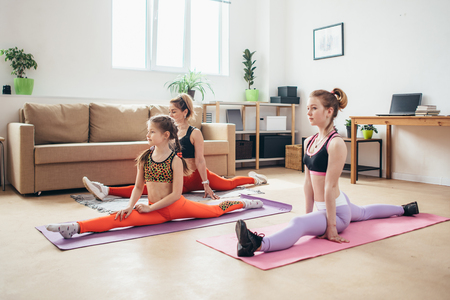Fit females doing splits. Mother and daughters exercising, stretching legs