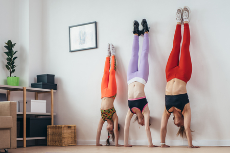 Females doing handstand pose near wall. Mother and daughters exercising at home, sport, family Imagens