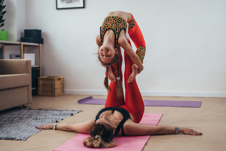 Mother and daughterdoing gymnastic exercises together at home