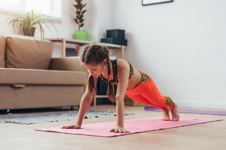 Little girl doing plank exercise at home. Stock Photo