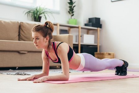 Fit girl doing plank exercise at home.