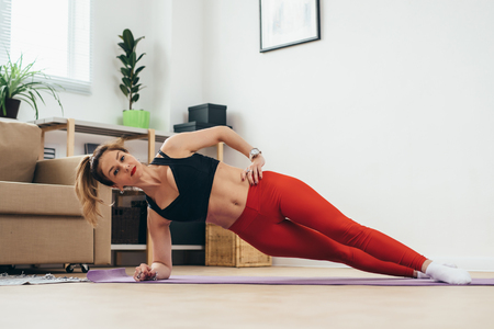 Fit woman doing plank exercise at home.
